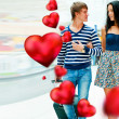 Portrait of young couple walking together at airport hall with their luggage. They are very happy to fly to warm country on holidays. Hearts around them. Valentine concept — Stock Photo