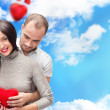 Stock Photo: Happy young adult couple with red heart on romantic background with sky and clouds, embracing and laughing