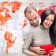 Portrait of young couple embracing and holding red heart. Standing against world map with photo of — Stock Photo