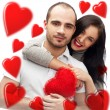 Stock Photo: Beautiful young love couple embracing against a white background and many red hearts flying around them