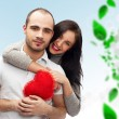 Happy young adult couple with red heart on background with green leaves, embracing and laughing - Stockfoto