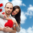 Happy young adult couple with red heart on romantic background with sky and clouds, embracing and laughing — Stock Photo