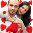 Beautiful young love couple embracing against a white background and many red hearts flying around them — Stock Photo #9254586