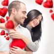 Beautiful young love couple embracing against a white background and many red hearts flying around them — Stock Photo #9254591
