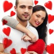 Beautiful young love couple embracing against a white background and many red hearts flying around them — Stock Photo