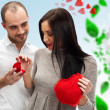 Proposal of marriage: young man putting ring on young ladys finger, on romantic background with red hearts and green leaves — Stock Photo