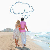 Couple at the beach holding hands and walking. Sunny day, bright colors. Europe, Spain, Costa Blanca. Blank cloud balloon overhead — Stock Photo