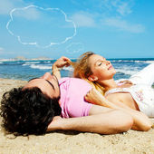 Young beautiful romantic couple relaxing on beach at sunny day. Blank cloud balloon overhead — Stock Photo