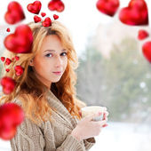 Portrait of beautiful red hair girl drinking coffee on winter background. Red hearts are flying around her. Valentine concept — Stock Photo