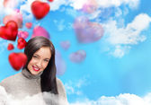 Happy young adult woman with red heart on romantic background with sky and clouds, laughing — Stock Photo