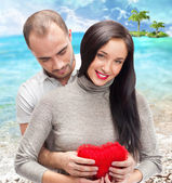 Portrait of young couple with red heart standing at tropical island and embracing — Stock Photo