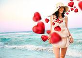 Mujer joven sonriente llevaba un sombrero de paja y divirtiéndose en la playa — Foto de Stock