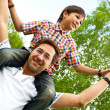 Portrait of smiling father giving his son piggyback ride outdoors against sky and trees in park — Stock Photo