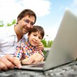 Closeup portrait of happy family: father and his son using laptop outdoor at their backyard sitting on the bench — Stock Photo
