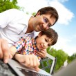 Closeup portrait of happy family: father and his son using laptop outdoor at their backyard sitting on the bench — Stockfoto