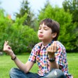 Stock Photo: Photo of adorable young wise boy sitting on the grass at his backyard