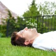 Close-up portrait of young good looking man in white shirt lying on lawn and daydreaming while looking at the sky — 图库照片