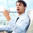 Young business man drinking water sitting relaxed on armchair at his modern office — Stock Photo #9270545