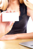 Young business woman showing blank business card to camera — Stock Photo