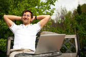 Portrait of a young man with laptop outdoor sitting on bench — Stock Photo