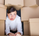Portrait of young woman surrounded by lots of boxes. Lots of work concept. — Stock Photo