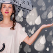 Portrait of beautiful young fashionable woman standing under umbrella and catching fake water drops of rain. Safety concept — Stock Photo
