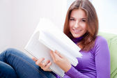 Young adult woman writing in her copybook while sitting on a large beanbag at her home — Stock Photo