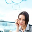 Portrait of a cheerful Business woman sitting on her desk with an at symbol and blank cloud balloon overhead — Stock Photo