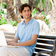 Portrait of a young man with laptop outdoor sitting on bench — Stock Photo #9493139