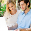 Young couple working on laptop and smiling while sitting relaxed on bench at summer park — Stock Photo