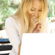 Beautiful woman using laptop while sitting relaxed on bench at summer park — Stock Photo