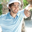 Young man wearing hat and casual clothes in sunny day. Leaning on palm tree at summer park — Foto Stock