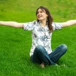 Full length of pretty young woman resting on grass and smiling. Greeting with opened arms — Stock Photo #9493800