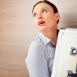 Portrait of emotional pretty young woman against modern stylish wooden wall holding big metal case — Stock Photo #9493884