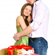 Portrait of young couple standing together and embracing. Gift boxes on foreground — Stock Photo