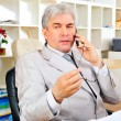 Portrait of a senior business man sitting by his phone in the office — Stock Photo