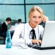 Portrait of beautiful woman using laptop at her workplace on the background of business — Stock Photo #9494442