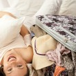 Beautiful young slim woman on the bed indoors unpacking clothes from suitcase — Stock Photo