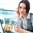 Portrait of a cheerful Business woman sitting on her desk with an at symbol — Stock Photo