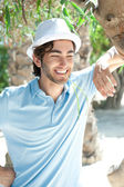Young man wearing hat and casual clothes in sunny day. Leaning on palm tree at summer park — Stock Photo