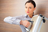 Portrait of emotional pretty young woman against modern stylish wooden wall holding big metal case — Stock Photo
