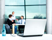 Modern laptop on foreground at empty workplace. Team of young businesspeople discussing plans on background — Stock Photo