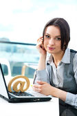 Portrait of a cheerful Business woman sitting on her desk with an at symbol — Fotografia Stock