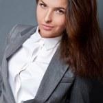 retrato de uma mulher de negócios jovem lindo encostado fundo cinza e posando na moda. olhando para a câmera — Foto Stock