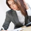Beautiful business woman signing documents working on computer at her office — Stock Photo