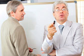 Closeup of two mature smiling business men standing at their office near white board. — Stock Photo