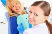 At dentist's office young nurse with adult mature woman, both looking at camera and smiling — Stock Photo