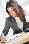 Mooie zakenvrouw ondertekenen van documenten werken op de computer op haar kantoor — Stockfoto