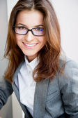 Beautiful young business woman wearing glasses sitting relaxed at her office and looking at camera — Stock Photo
