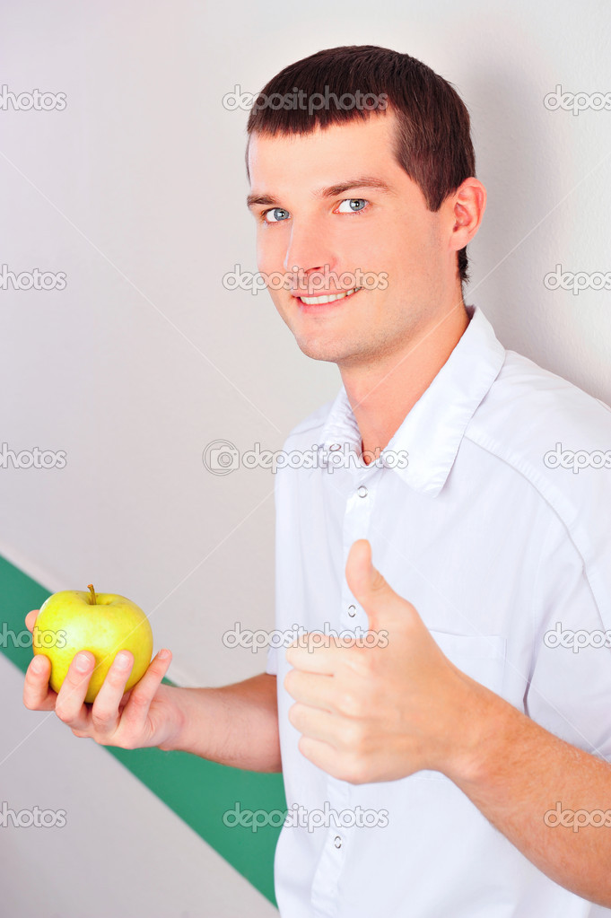 Closeup portrait of a happy adult dentist man leaning wall at dental clinic and holding green apple — Stock Photo #9579623